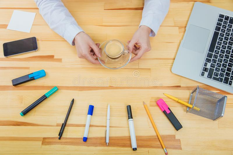 Wooden beautiful table. It has a laptop, a feather, markers, a coffee cup, pencil, phone ,a gray laptop and a women`s. Wooden beautiful table. It has a laptop, a stock photography