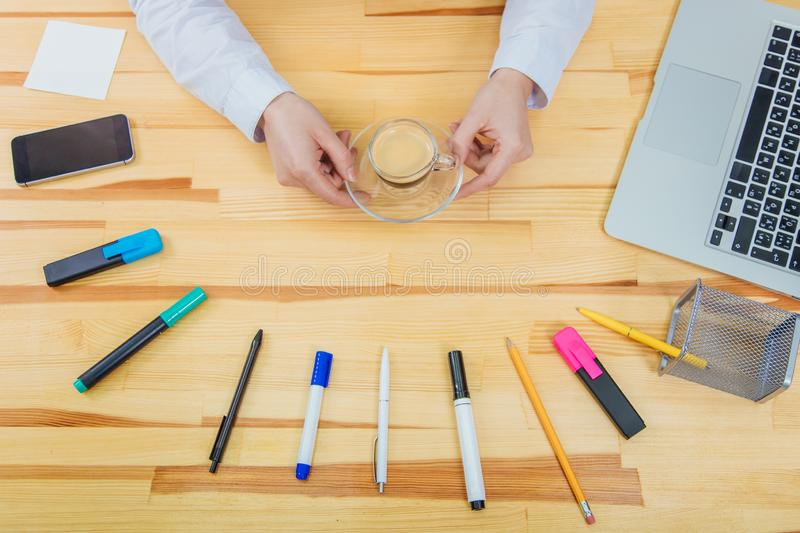 Wooden beautiful table. It has a laptop, a feather, markers, a coffee cup, pencil, phone ,a gray laptop and a women`s. Wooden beautiful table. It has a laptop, a stock images