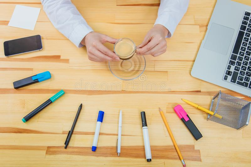 Wooden beautiful table. It has a laptop, a feather, markers, a coffee cup, pencil, phone ,a gray laptop and a women`s. Youth hand holding a baby glove. Top view royalty free stock images