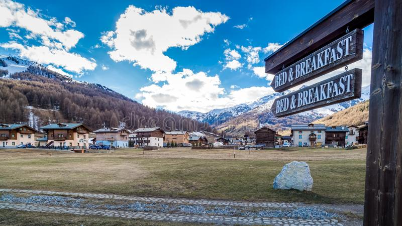 Bed and Breakfast sign pointing to Livigno village, old wooden houses, Italy, Alps. Wooden Bed and Breakfast sign pointing to Livigno village, Italian Alpine ski royalty free stock photos