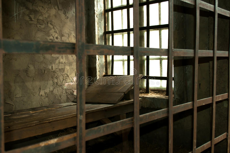 Wooden bed in a medieval prison cell royalty free stock photography