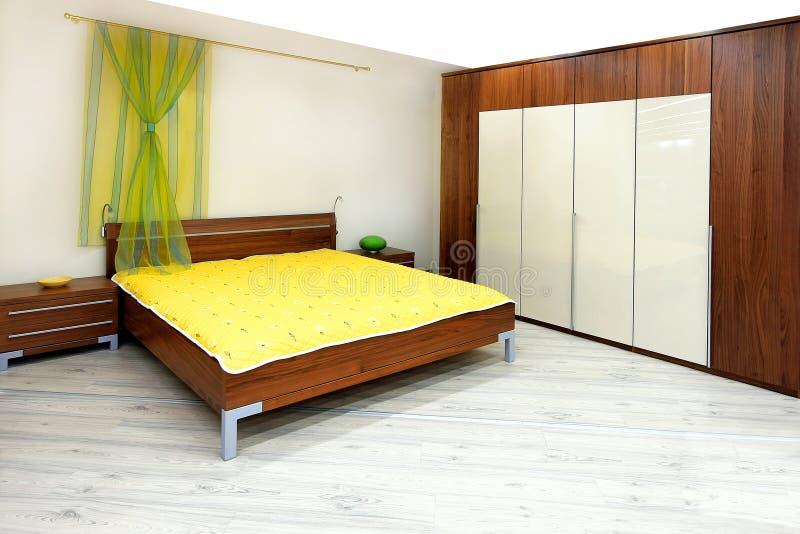 Wooden bedroom. Interior shot of bedroom in brown wood royalty free stock image