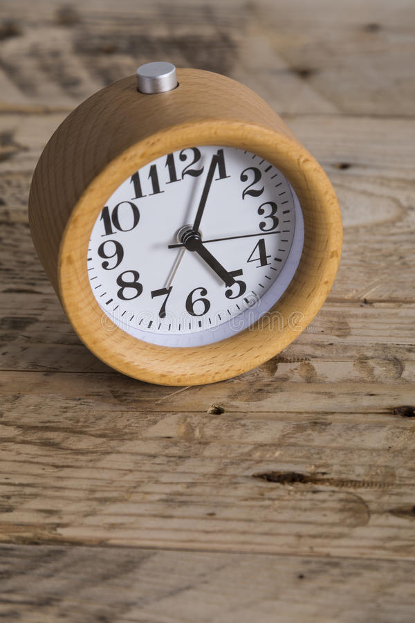 Wooden bedside clock. Bedside table alarm clock on a wooden table stock photo