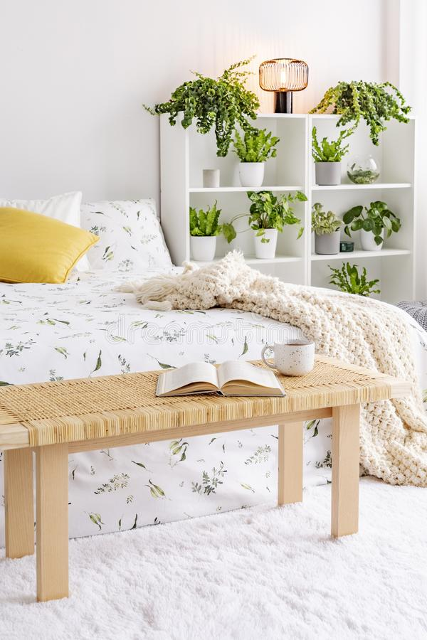 A wooden bedside table with a book and a cup in front of a bed in a natural bedroom interior with many green plants in pots. Real royalty free stock photo