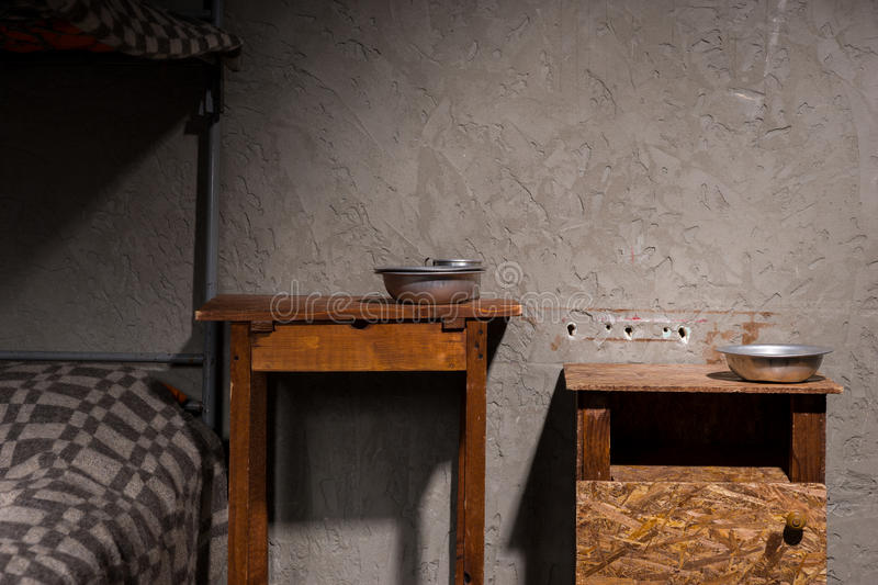 Wooden bedside tables with aluminum dishes near iron bunk bed in stock photography