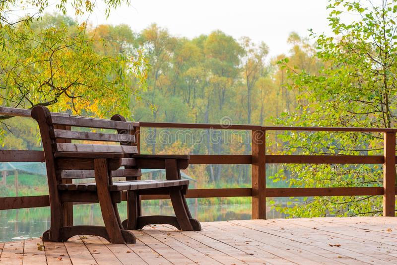 Wooden bench on a bridge over a lake. In an autumn park stock photos