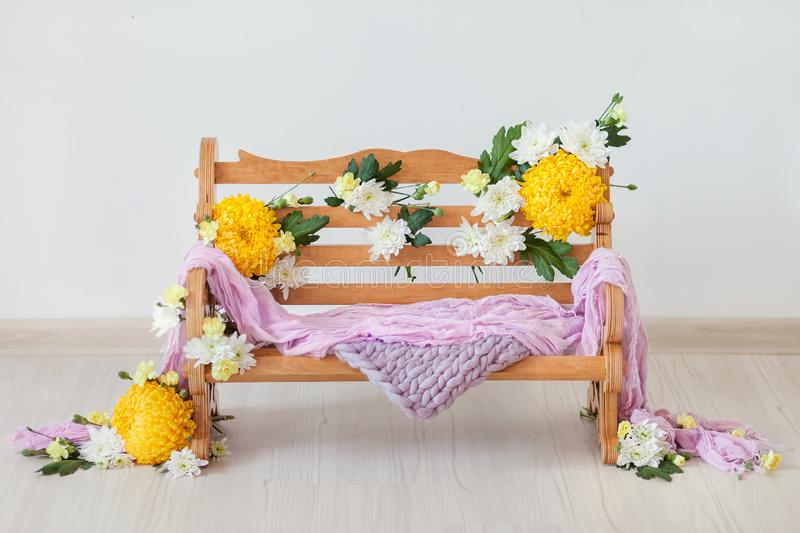 A wooden bench decorated with yellow and white chrysanthemums flowers. On a light background with the addition of lilac fabric props for shooting newborns and stock photos