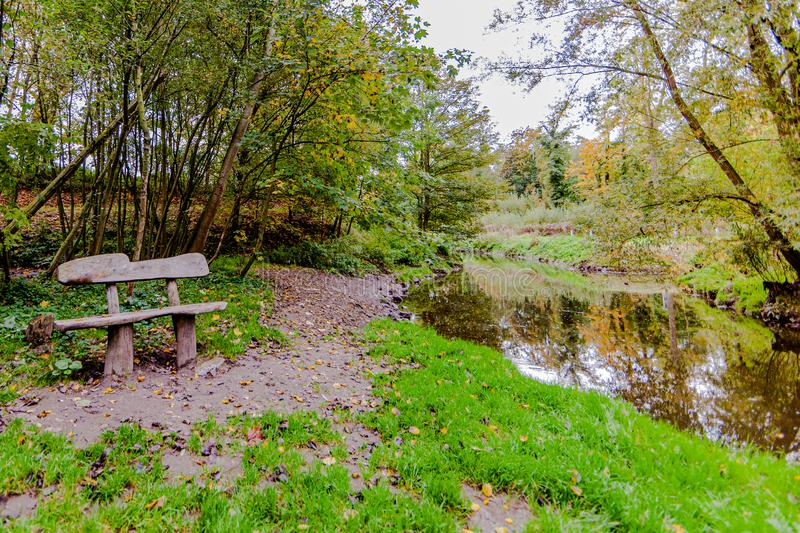 Wooden bench at the edge of a quiet river with reflection in the water royalty free stock photography