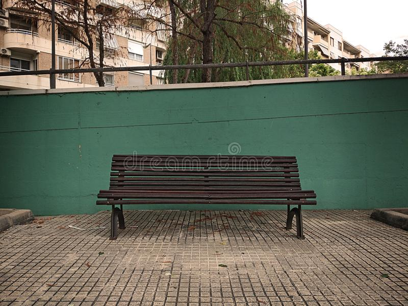 Wooden bench in front of a green concrete wall with leaves on the ground and located in an urban park royalty free stock images