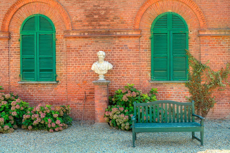 Wooden Bench Stand On The Gravel In Front Of Red Brick House With Closed  Green Shutters In Park Of Racconigi In Piedmont, Northern Italy.