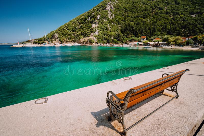 Wooden bench in front of the sea. Ecovillage at Ithaca island in Greece. Picturesque mediterranean town.  stock images