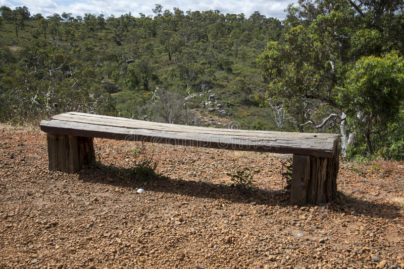 A wooden bench in John Forrest National Park. A wooden bench looking at forest landscape background in John Forrest National Park, Perth Hills, Western Australia stock image