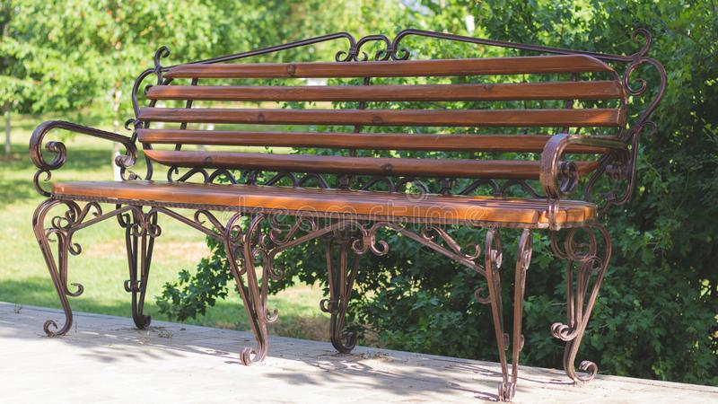 Wooden bench with metal art forging in the amusement park. Brown bench on the green background of nature royalty free stock photo