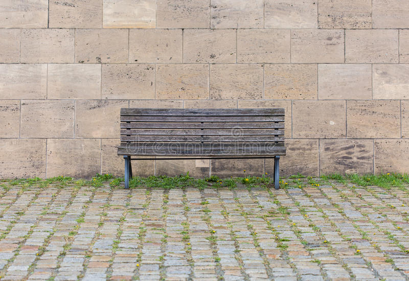 A wooden bench. Near stone wall stock photo