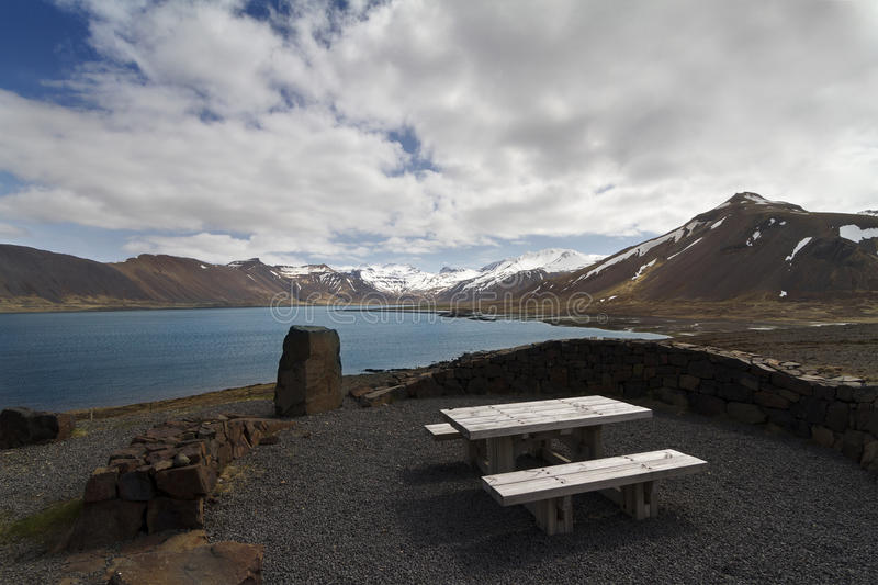 Wooden bench next to a beautiful lake panorama in Iceland. Horizontal panorama of a wooden resting bench next to a lake and mountains covered in snow in Iceland stock photos