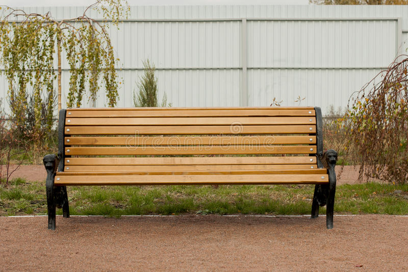 Wooden bench outdoor. Wooden bench in front of a fence royalty free stock photos