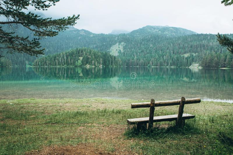 A wooden bench overlooking a lake royalty free stock images