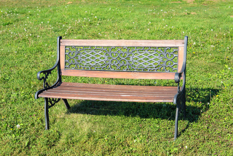 Wooden bench in park. Wooden bench on the green field royalty free stock photography