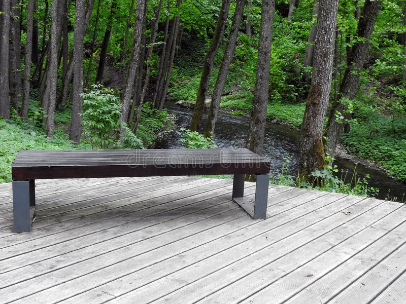 Wooden bench in park, Lithuania. Beautiful wooden bench near small river in park in Druskininkai town royalty free stock photo