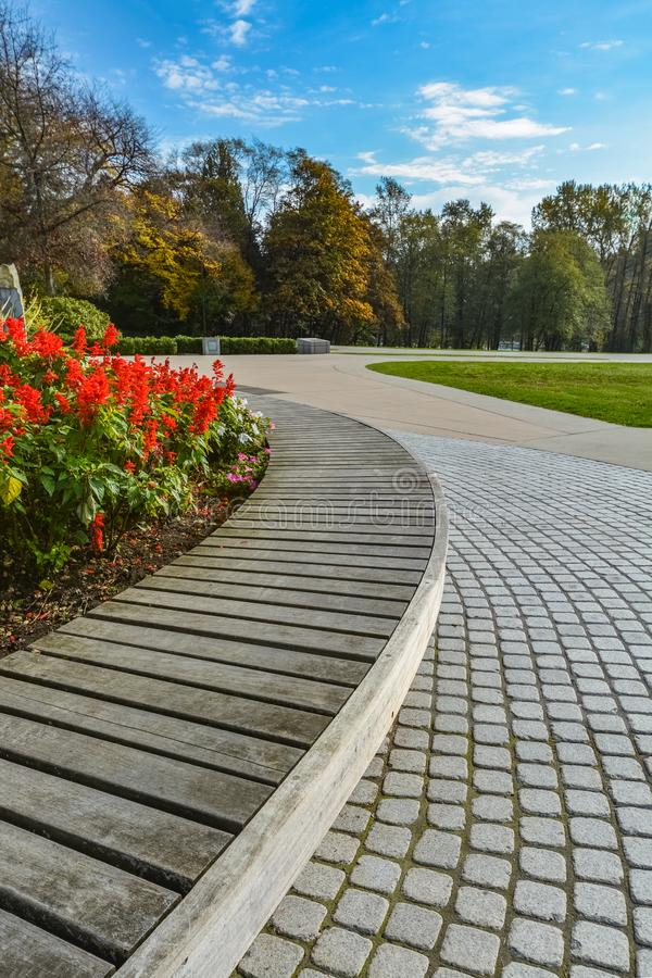 Wooden bench and paved pathway on autumn season in the park stock photography