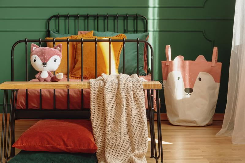 Wooden bench with plush toy and blanket in the food of single metal bed stock photo