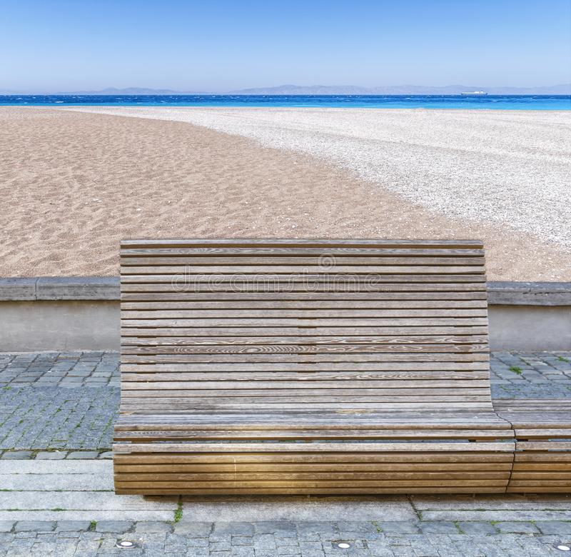 Wooden bench on public promenade with beach and sea background stock photo