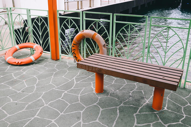 Wooden bench with sea rescue item safety tube in Hong kong. Wooden bench with sea rescue item safety tube stock image