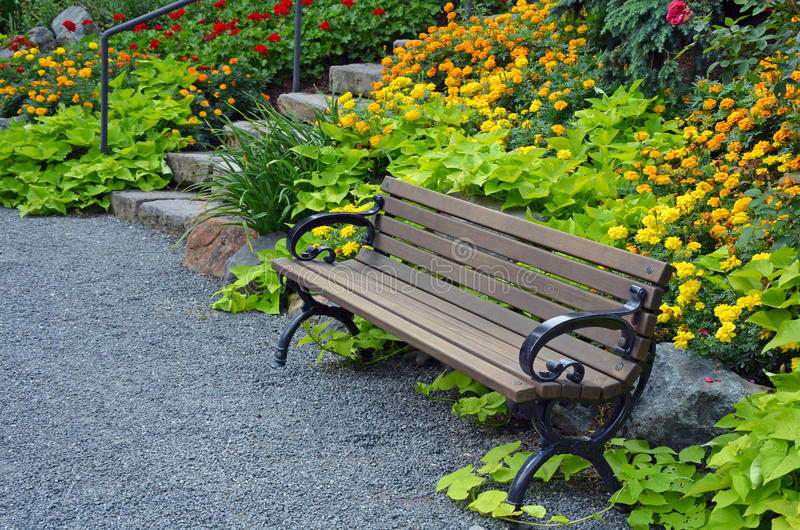 Wooden bench in summer garden. Wooden garden bench in colorful botanical summer garden stock photos