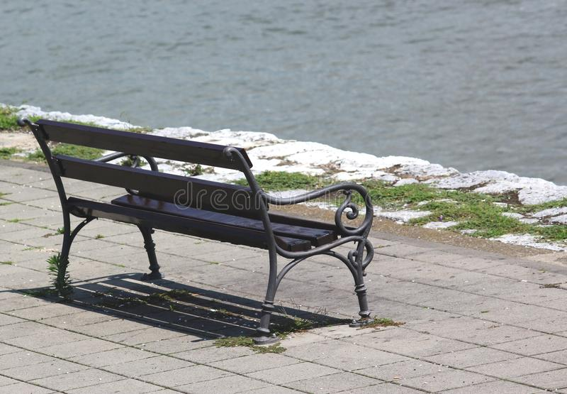 Wooden bench on the waterfront overlooking the river stock image