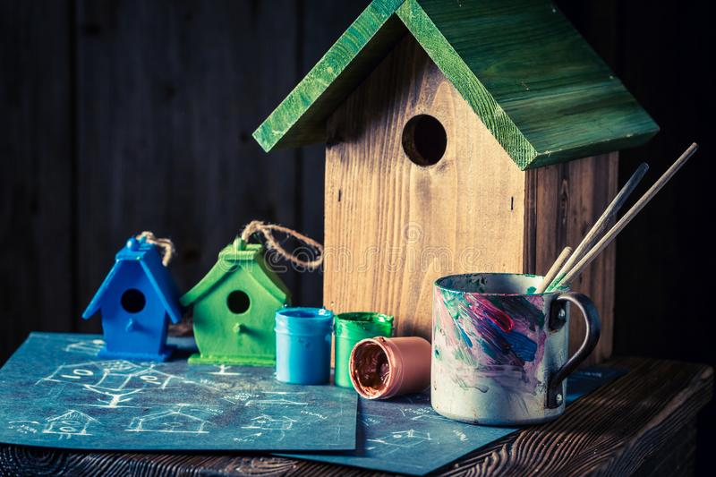 Wooden bird feeder and blue plan to build it. Closeup of wooden bird feeder and blue plan to build it royalty free stock photos