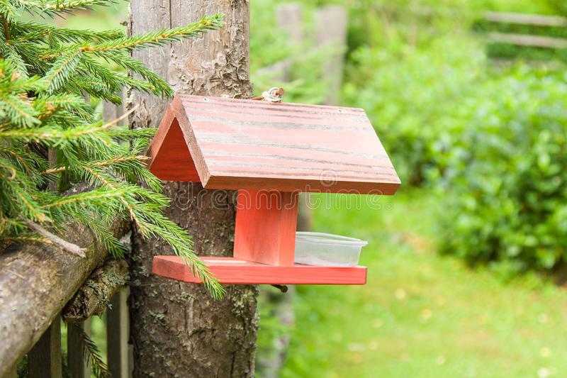 Wooden bird feeder hanging on the fence in summer garden. Wooden bird feeder hanging on the fence in green summer garden royalty free stock photography
