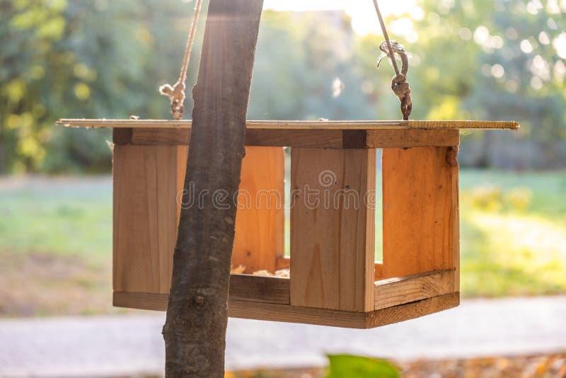 Wooden bird feeder house on a tree in autumn park. Animal wildlife care concept.  stock photos