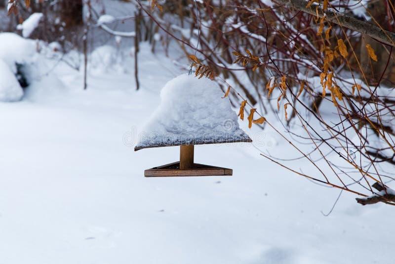 Wooden Bird feeder in the winter snow garden. royalty free stock images