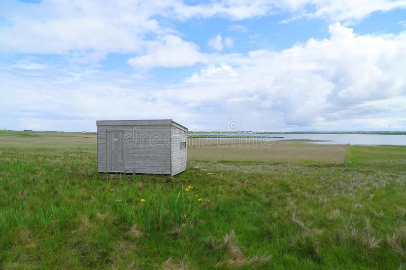 Wooden bird hide for bird watchers. Bird hide on the shores of Loch Bhasapoll on the island of Tiree in the Inner Hebrides of Scotland stock photo