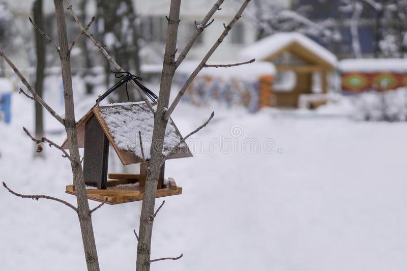 Wooden birdhouse with bird feeder hanging on the tree in winter park. Wooden birdhouse with bird feeder hanging on the tree in winter city park royalty free stock images