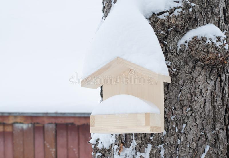 Wooden birdhouse hanging in the tree, covered with snow in winter royalty free stock photography