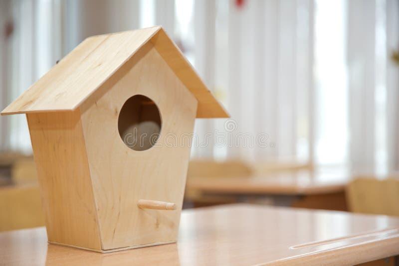 Wooden birdhouse . Little bird house hanging amidst branches . Wooden bird`s nest stock photography