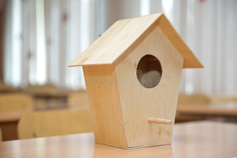 Wooden birdhouse . Little bird house hanging amidst branches . Wooden bird`s nest royalty free stock photography