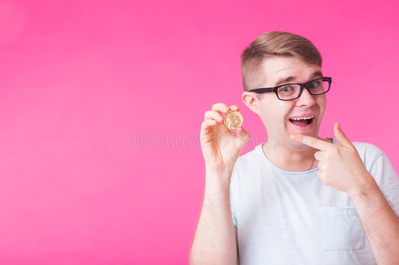 Wooden Bitcoin in funny man hand, Digital symbol of a new virtual currency.  stock image
