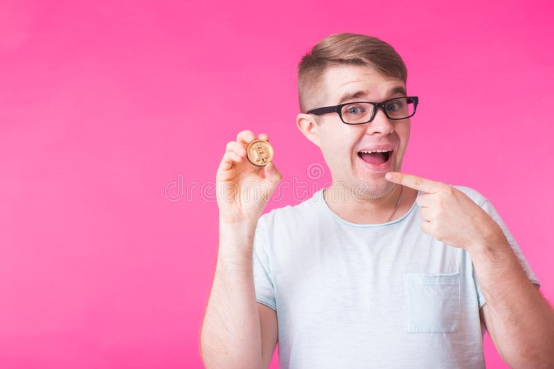 Wooden Bitcoin in funny man hand, Digital symbol of a new virtual currency.  royalty free stock image
