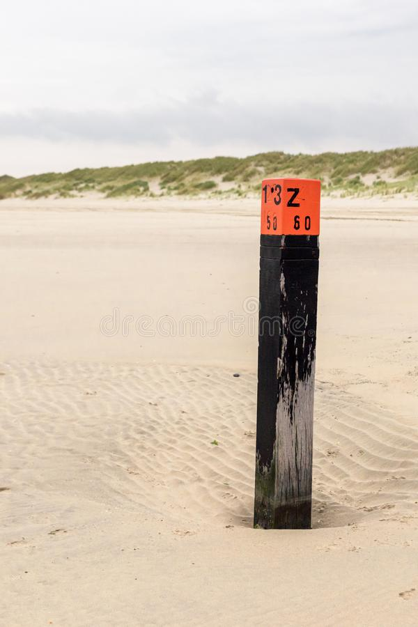 A wooden black pole with red head stands on the beach at the North Sea royalty free stock photo