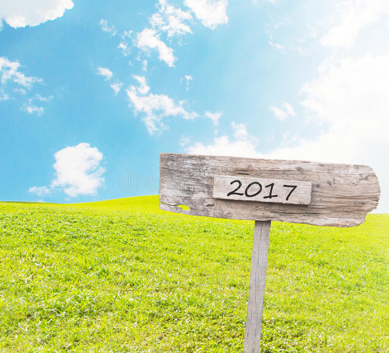 Wooden Blank Sign With Text 2017 Over Green Grass field royalty free stock images