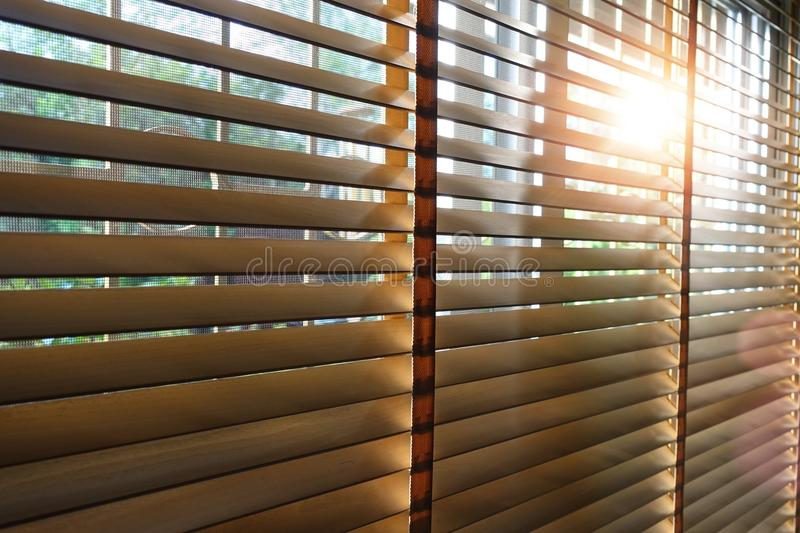 Wooden blinds in a home catching the sunlight with burst light stock images