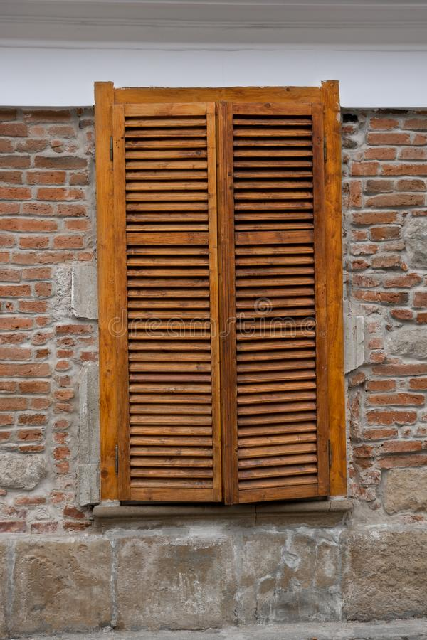 Wooden blinds on windows on the street royalty free stock photo