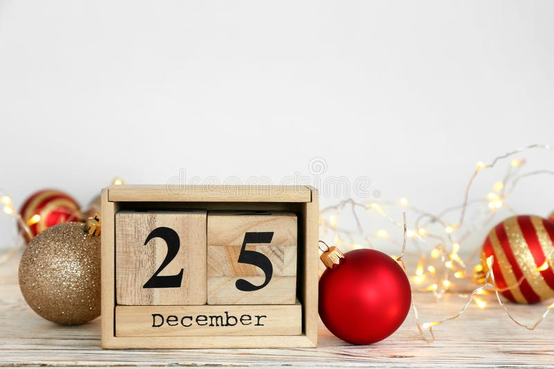 Wooden block calendar and festive decor on table. Christmas countdown royalty free stock photography