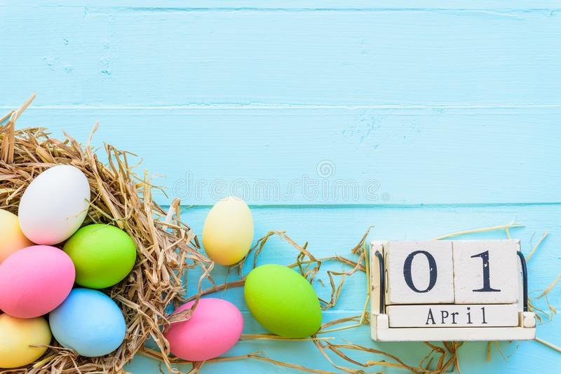 Wooden block calendar for Easter Day, April 1. Colorful of Easter eggs in nest on pastel color bright blue and white wooden royalty free stock image