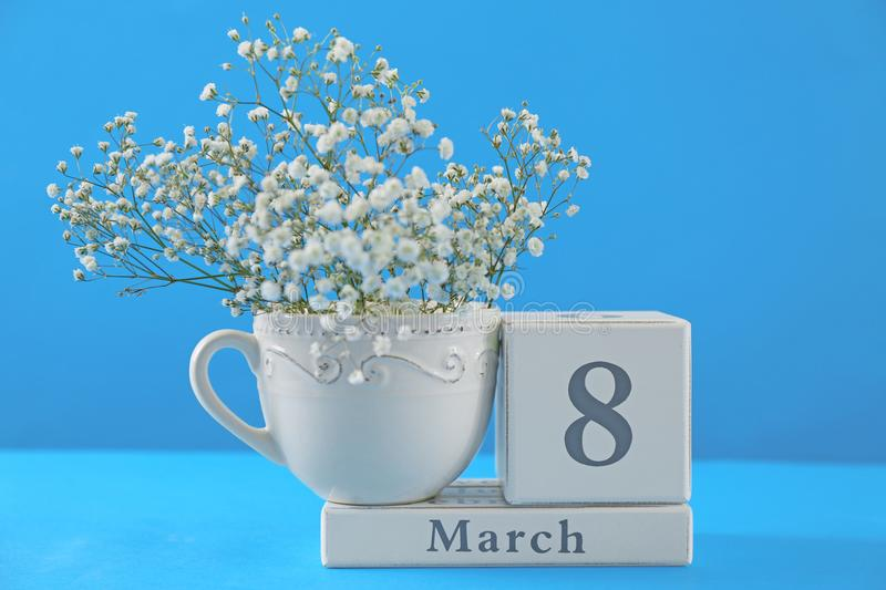 Wooden block calendar and flowers. On color background. International Women`s Day celebration royalty free stock photos