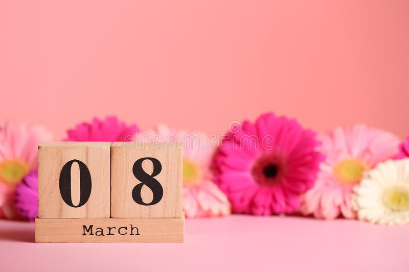 Wooden block calendar and flowers on table against color background, space for text. royalty free stock photos