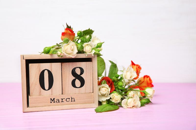 Wooden block calendar and roses on tabl. E. Composition for International Women's Day royalty free stock photo