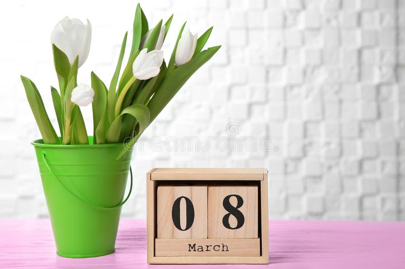 Wooden block calendar and tulips on table. Composition for International Women's Day royalty free stock photography